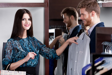 Young man consults with girlfriend while selecting a shirt
