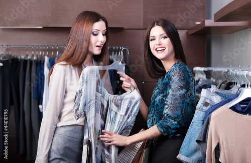Friends do shopping and discuss a dress at the store