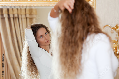 Beautiful woman looking in the mirror