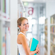 Pretty young college student in a library (shallow DOF; color to