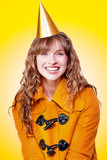 Laughing winter party girl on yellow background