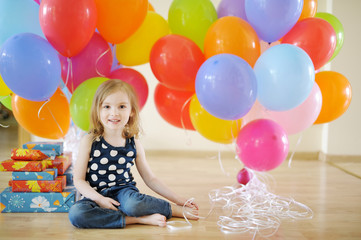 Little birthday girl with tons of balloons