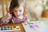 Fototapety Cute little girl is drawing with paints
