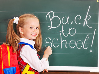 Child writting on blackboard.