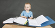 baby with paperwork at wooden desk