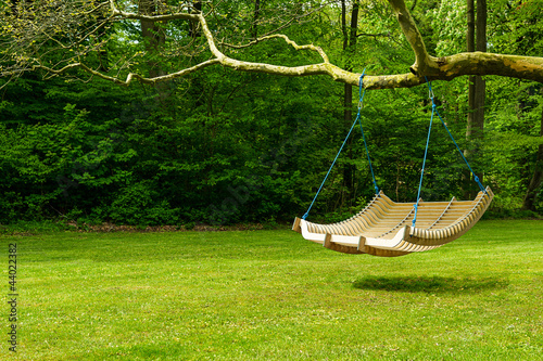 Swing bench in lush garden - 44022382