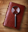 Notebook with a magnifier on wood table