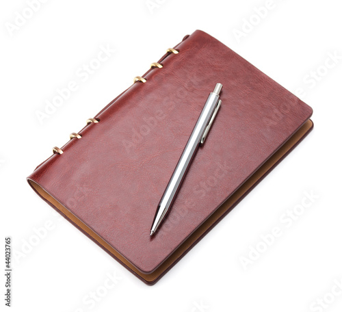 Brown notepad and pen on white background with soft shadow