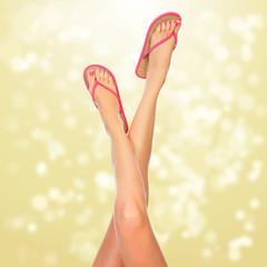 Female legs with pink flip-flops