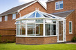 Conservatory with glass roof against a red brick house - 44026735
