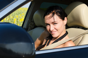 Smiling woman in a motor car