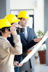 architect looking at construction site with binoculars