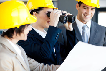 construction manager viewing construction site with binoculars