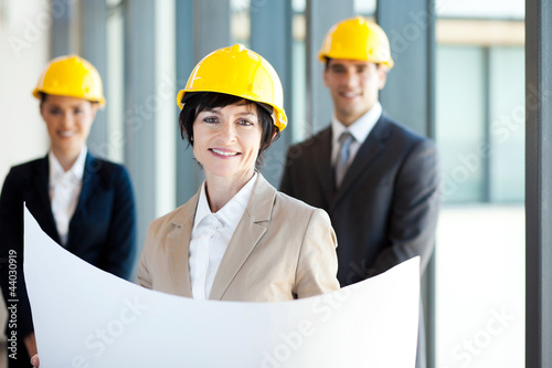 middle aged construction businesswoman holding blue print