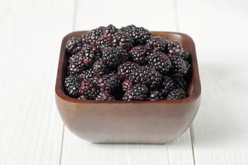 pile of blackberries on wooden bowl