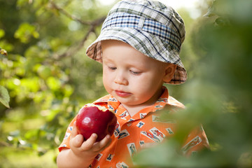 Little boy in panama with red apple