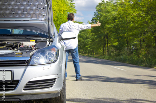 Man hitchhiking near a broken car