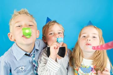 drei Kinder mit Tröten