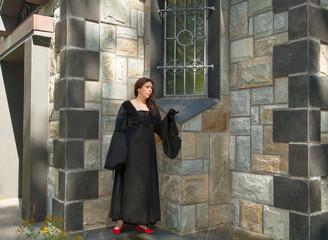 Eine schwarz gekleidete Frau steht vor einem Mausoleum