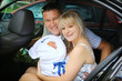 Happy family with newborn in car