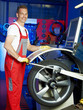Master mechanic fitting a tyre in a garage with counterbalancing