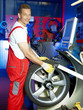 Car mechanic fitting a tyre in a garage with counterbalancing