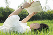Beautiful young woman reading a book on nature