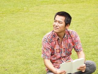 芝生の上で読書をする男性