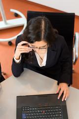 Geschäftsfrau sitzt im Büro an einem Schreibtisch