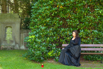 Eine einsame Frau sitzt auf einer Friedhofsbank