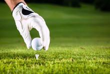 Hand hält Golfball auf Golfplatz mit Tee