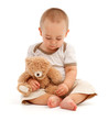 Little boy playing with toy bear