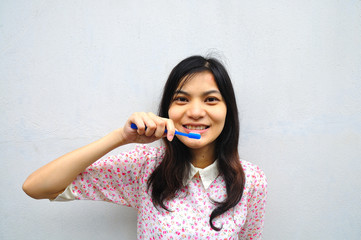 portrait of woman smiling brushing her teeth