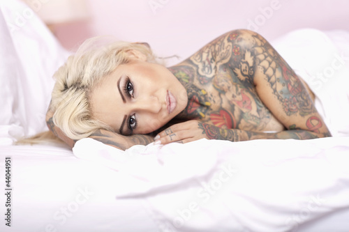 Portrait of naked female with tattoo lying on bed