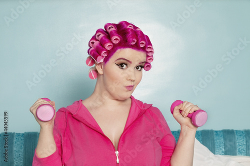 Portrait of a young woman exercising with dumbbell