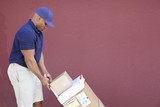 Side view of muscular African American delivery man with handtruck