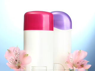 deodorants with flowers on blue background