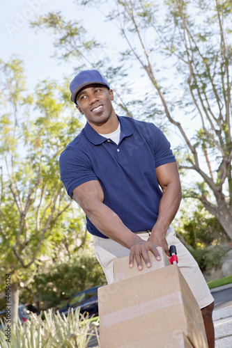 Happy young African American male pushing handtruck