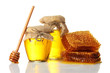 sweet honeycombs, wooden drizzler, and jars with honey,