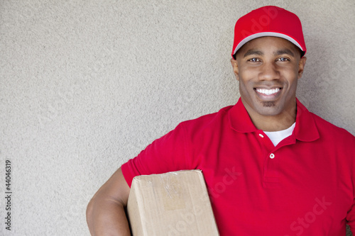 Portrait of a African American delivery man holding package against wall