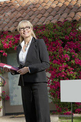 Happy senior real estate agent looking away with house in background