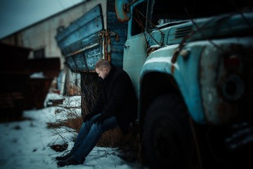 Man in depression sitting on old car