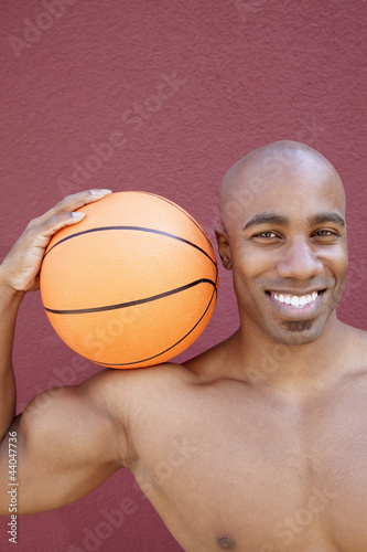 Portrait of a happy African American man with basketball on shoulder over colored background