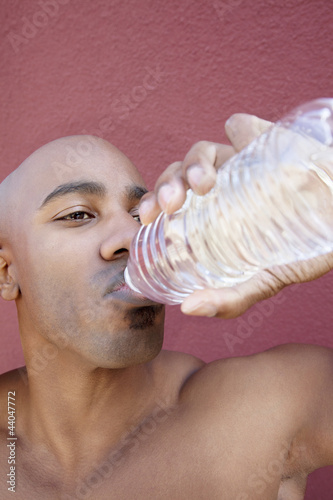 Young African American man drinking water from bottle over colored background
