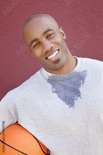 Portrait of a happy young African American man with basketball over colored background