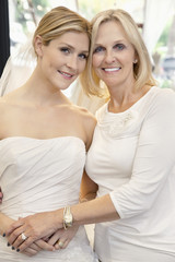 Portrait of a mother with daughter dressed as bride in bridal store