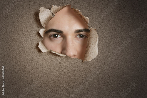 Portrait of a young Caucasian man peeking from ripped paper hole