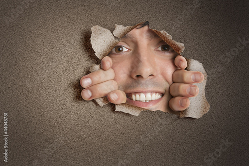 Portrait of a happy young Hispanic man peeking from ripped paper hole
