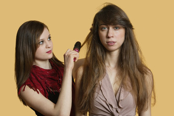 Portrait of a young female model getting her hair styled over colored background