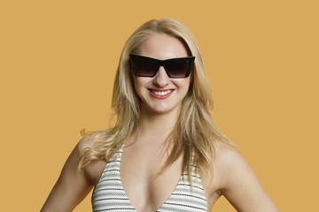 Portrait of a beautiful young woman in bikini wearing sunglasses over colored background